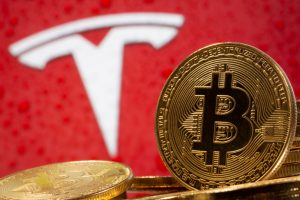 Representations of virtual currency Bitcoin are seen in front of Tesla logo in this illustration taken, February 9, 2021. REUTERS/Dado Ruvic/Illustration